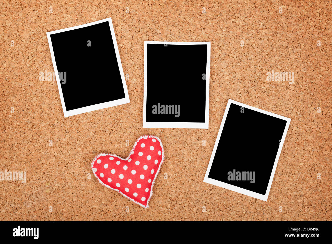Polaroid photo frames on cork texture background with handmaded heart - Stock Image