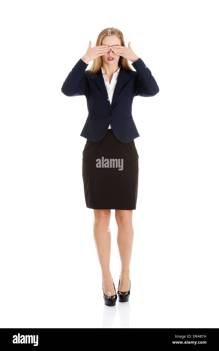 Beautiful business woman covering her eyes. Isolated on white. - Stock Image