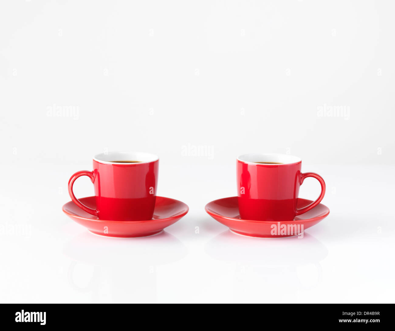 Two red small espresso coffee cups isolated on white background - Stock Image
