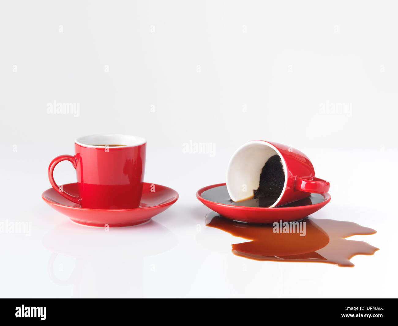 two red espresso coffee cups one cup with spilled coffee isolated
