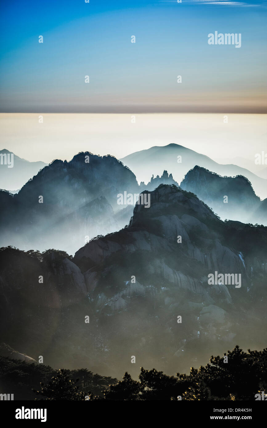Fog rolling over rocky mountains, Huangshan, Anhui, China, - Stock Image