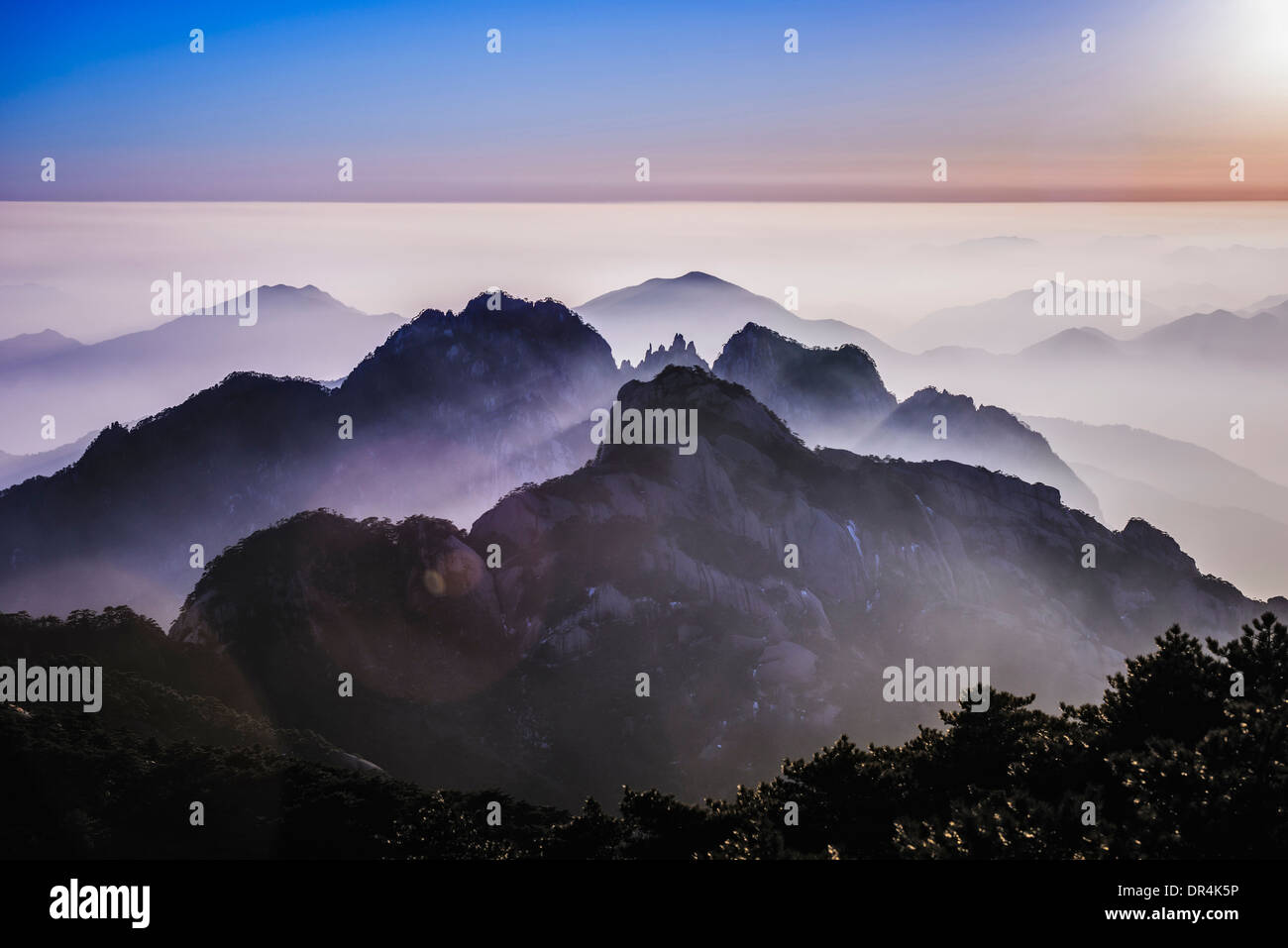 Fog rolling over rocky mountains, Huangshan, Anhui, China - Stock Image