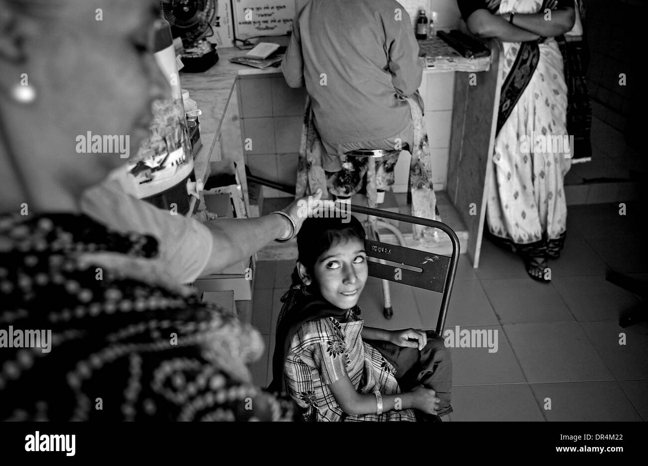 Jan 24, 2009 - DOTS centre,Ahmedabad, Gujarat, India - Touch of concern and a silent prayer, Munni being lovingly consoled by her Grandmother Sangitaben at the DOTS centre at Ahmedabad. The extra pulmonary TB has affected Munni's  spinal cord and that is affecting the physical control and movement of her eyes as well.She finds it difficult to stand and walk. After having cured of T - Stock Image