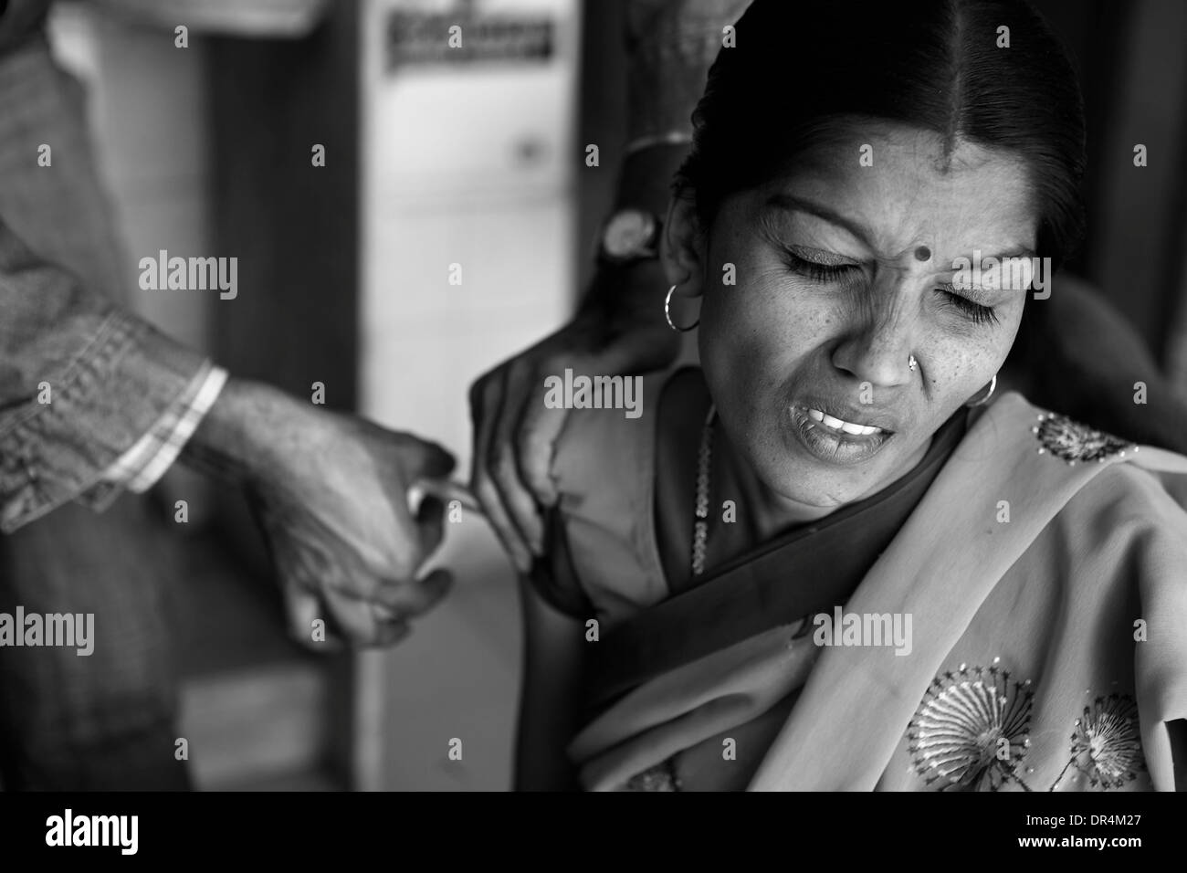 Jan 24, 2009 - DOTS centre,Ahmedabad, Gujarat, India - CHAMCHAMBEN SHARMA in pain as she is injected with the TB medicine she suffers from MDR-TB,She is enable to come to the fact that though regular with her CAT I and II regimes she has MDR-TB. (Credit Image: © Subhash Sharma/ZUMA Press) - Stock Image