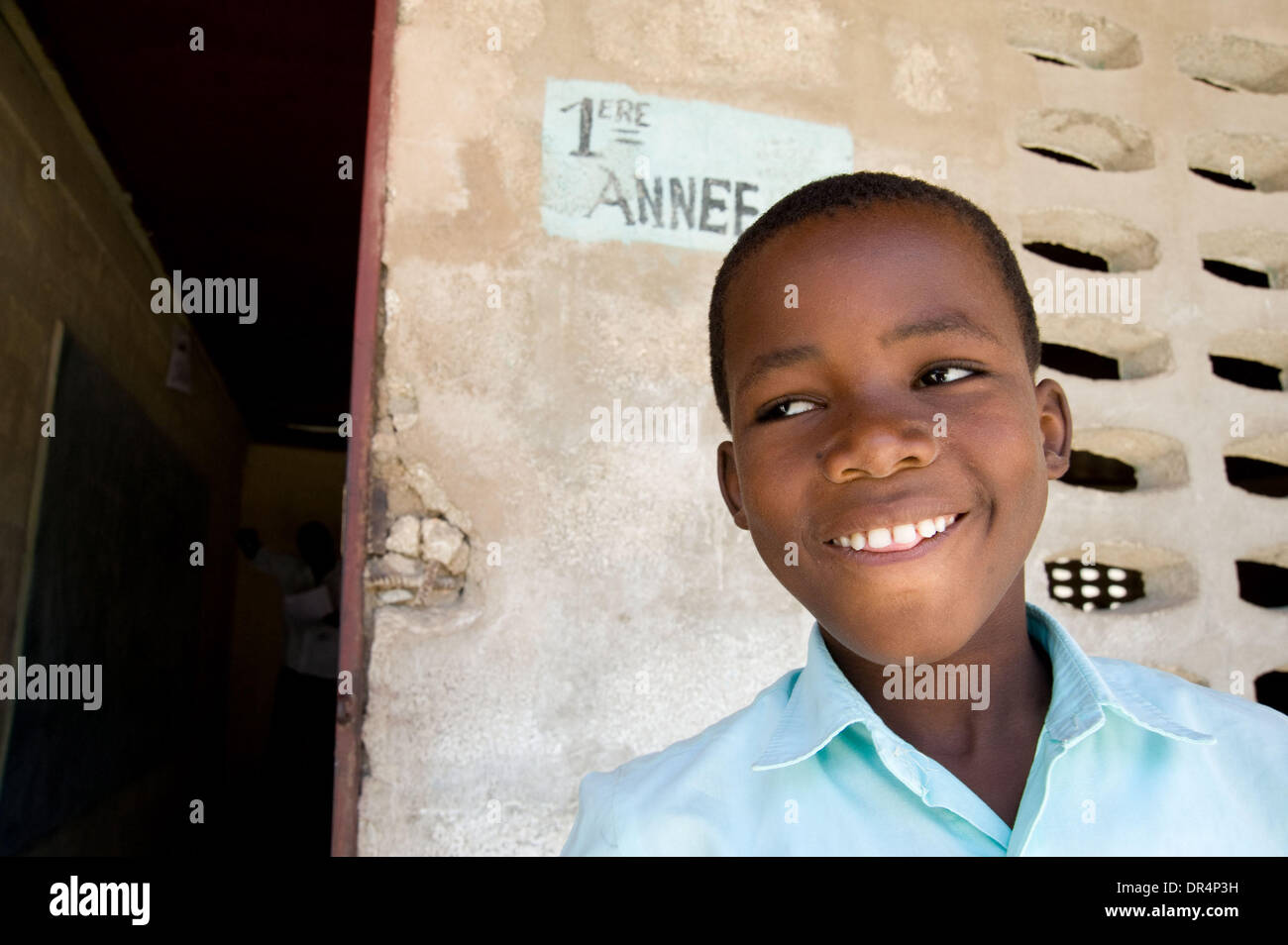 Apr 21, 2009 - Gonaives, Haiti - A young male student, boy, stands outside of his classroom at  a primary school Stock Photo