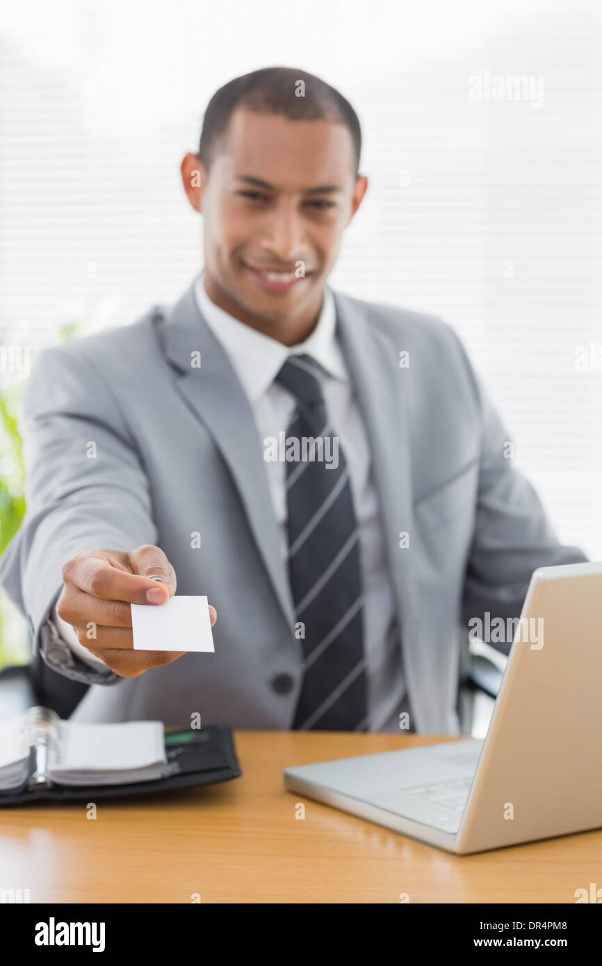 Well dressed man handing his business card at office desk - Stock Image