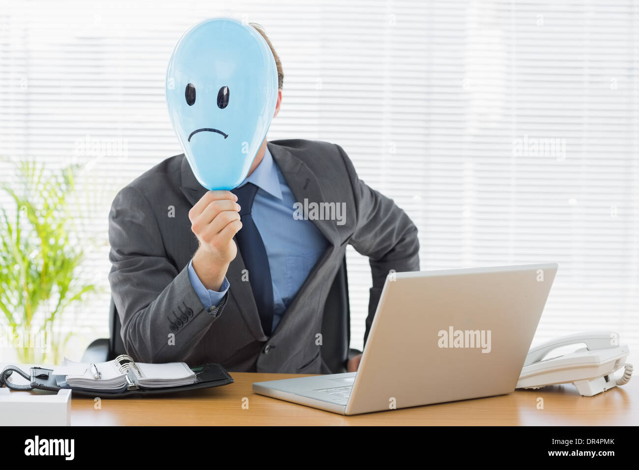 Businessman holding sad smiley faced balloon at office - Stock Image