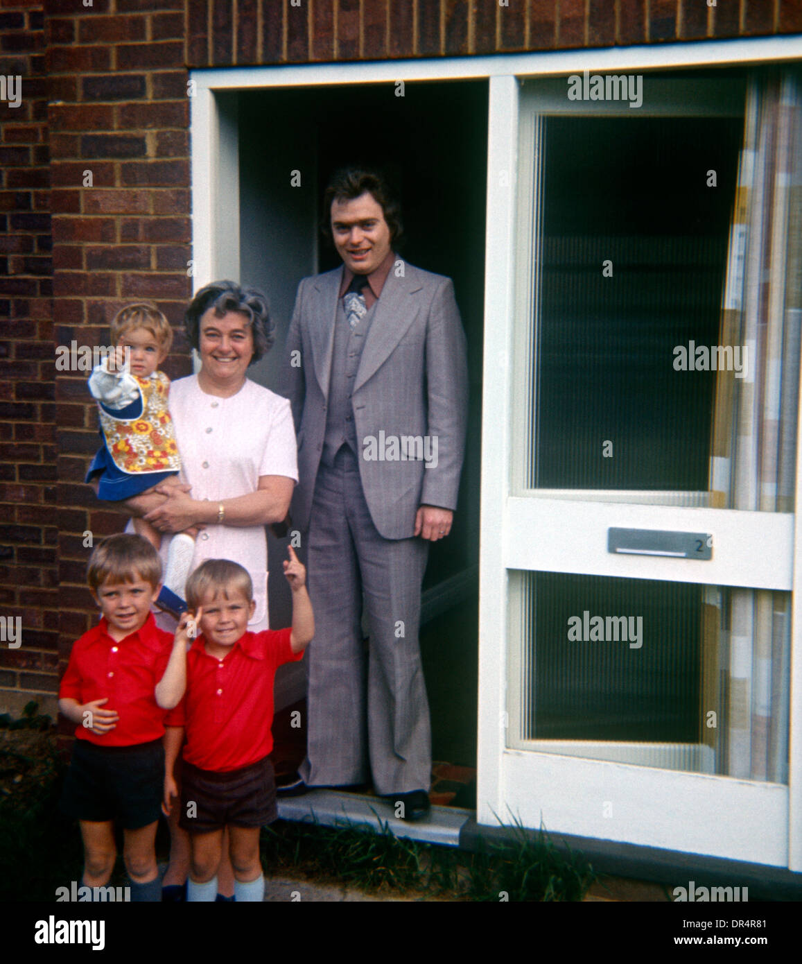 A portrait of family standing in the doorway of a detached home in the 1970s. - Stock Image