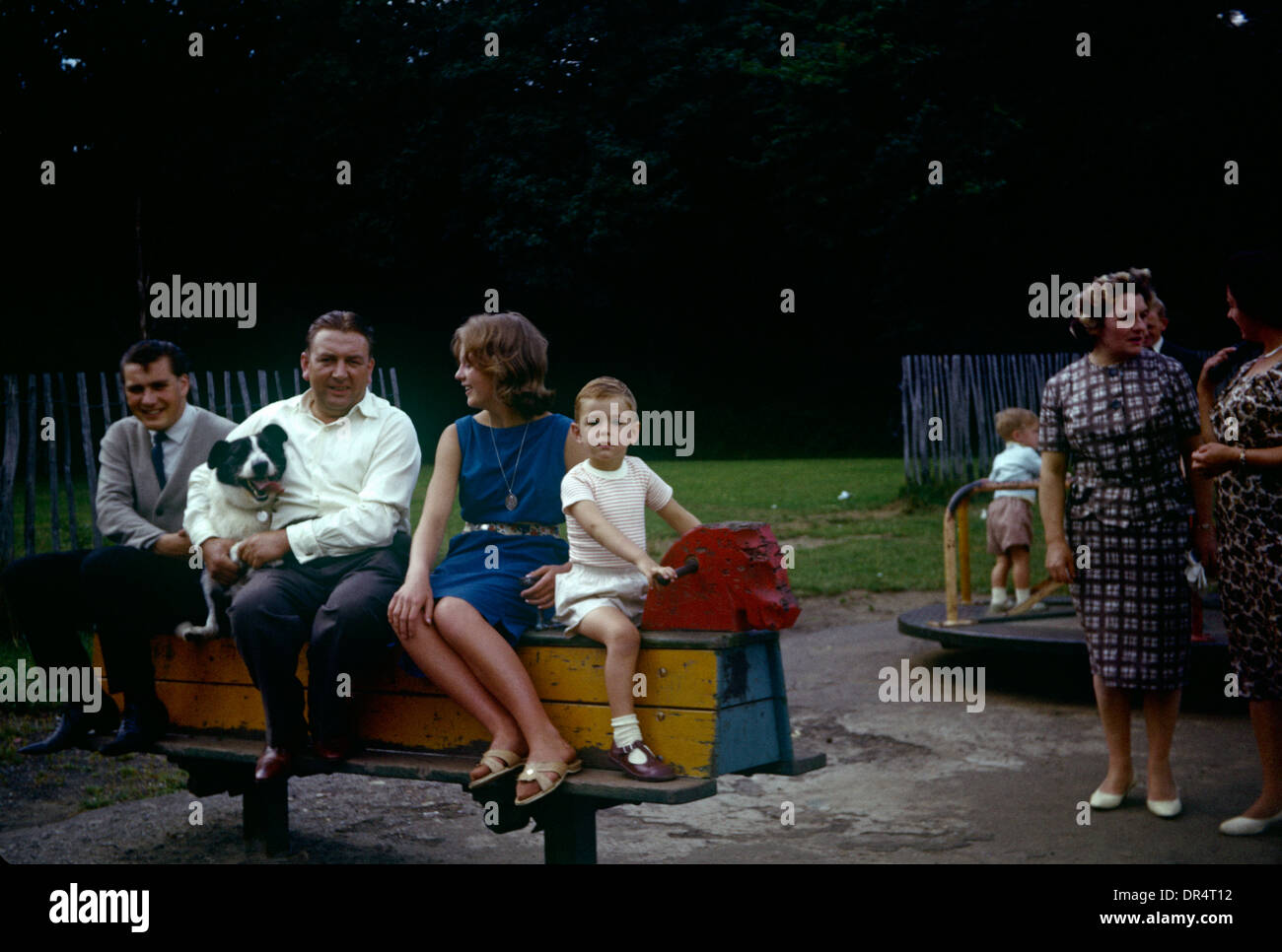 Family and friends sit on a rocking horse in a playground during summer time in the early 1960s. - Stock Image