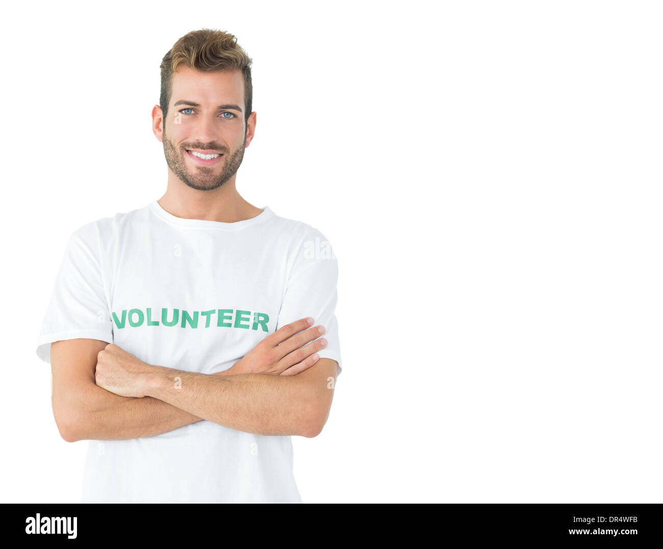 Portrait of a happy male volunteer standing with hands crossed - Stock Image
