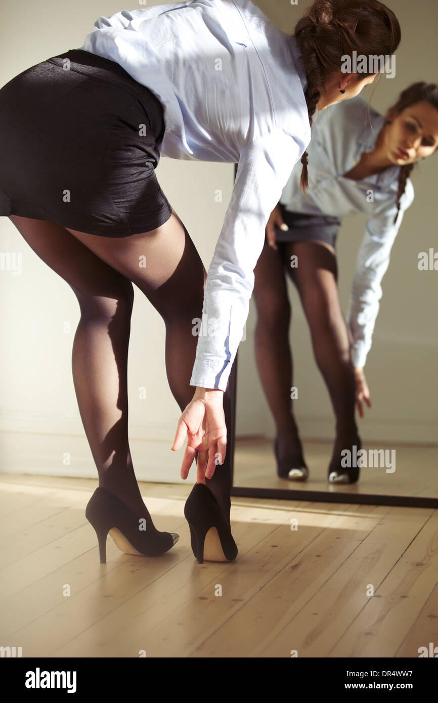 Attractive young businesswoman looking in to mirror while wearing high heels shoes. Caucasian female model getting dressed. - Stock Image