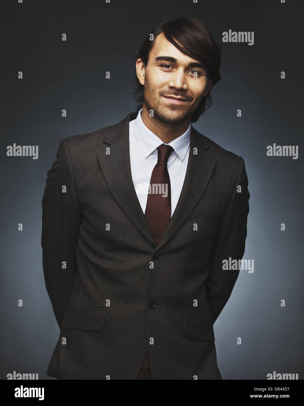 Portrait of charming young businessman looking at camera smiling. Well dressed asian male model posing against black background - Stock Image
