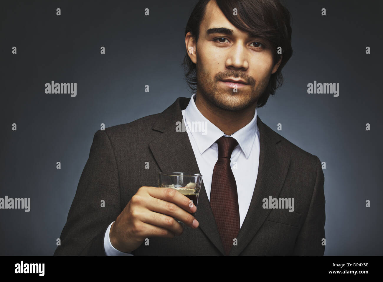 Closeup portrait of attractive young man in business suit holding a cup of coffee in hand. Asian male business executive - Stock Image