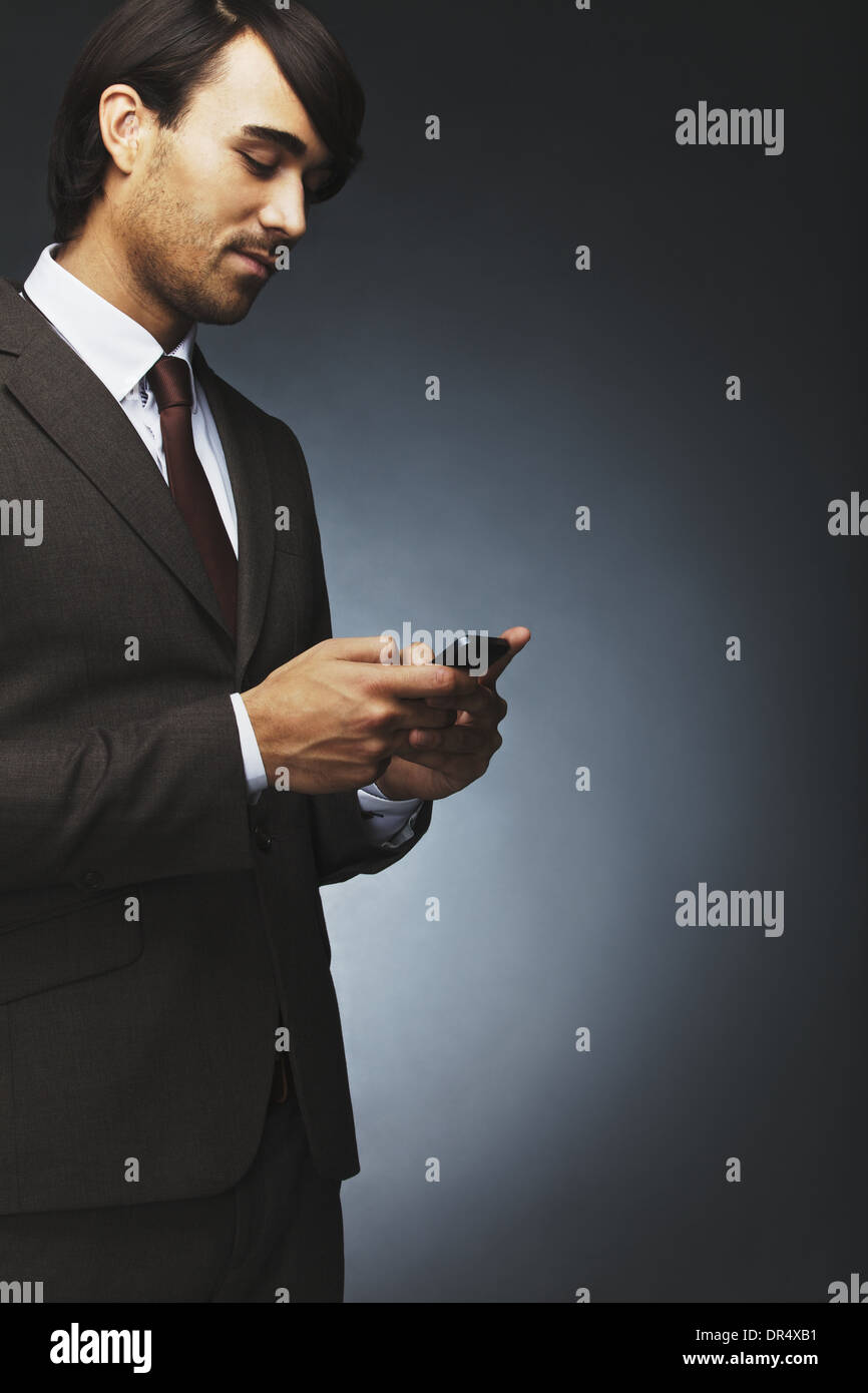 Portrait of young businessman text messaging using mobile phone on black background. Asian male model using cell phone. - Stock Image