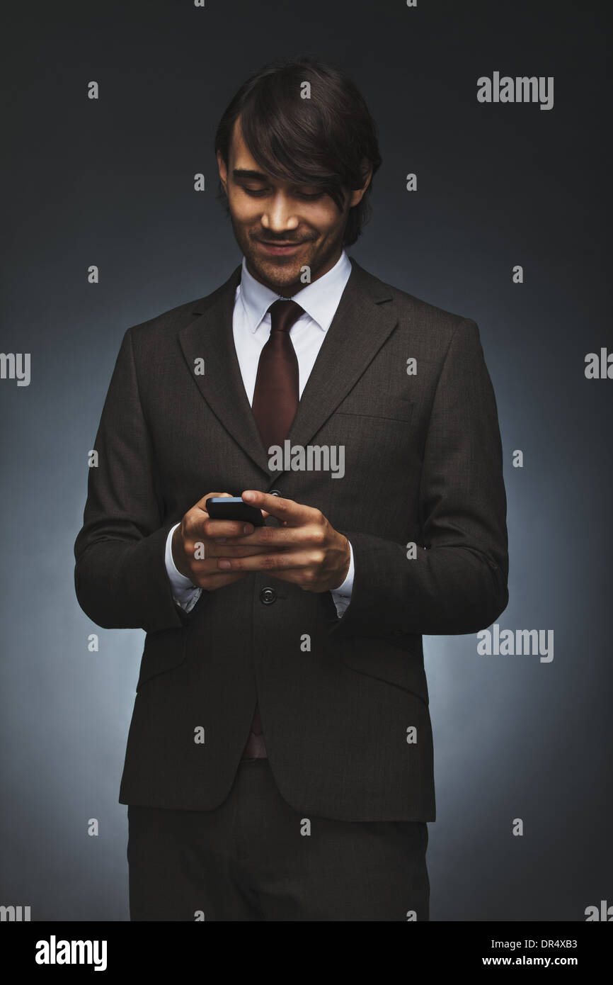 Happy young executive texting on his smart phone. Handsome male associate reading test message on his cell phone. - Stock Image