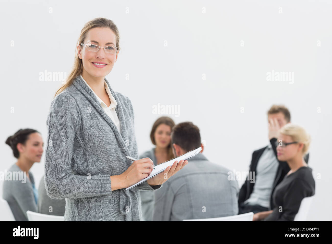Portrait of therapist with group therapy in session in background - Stock Image