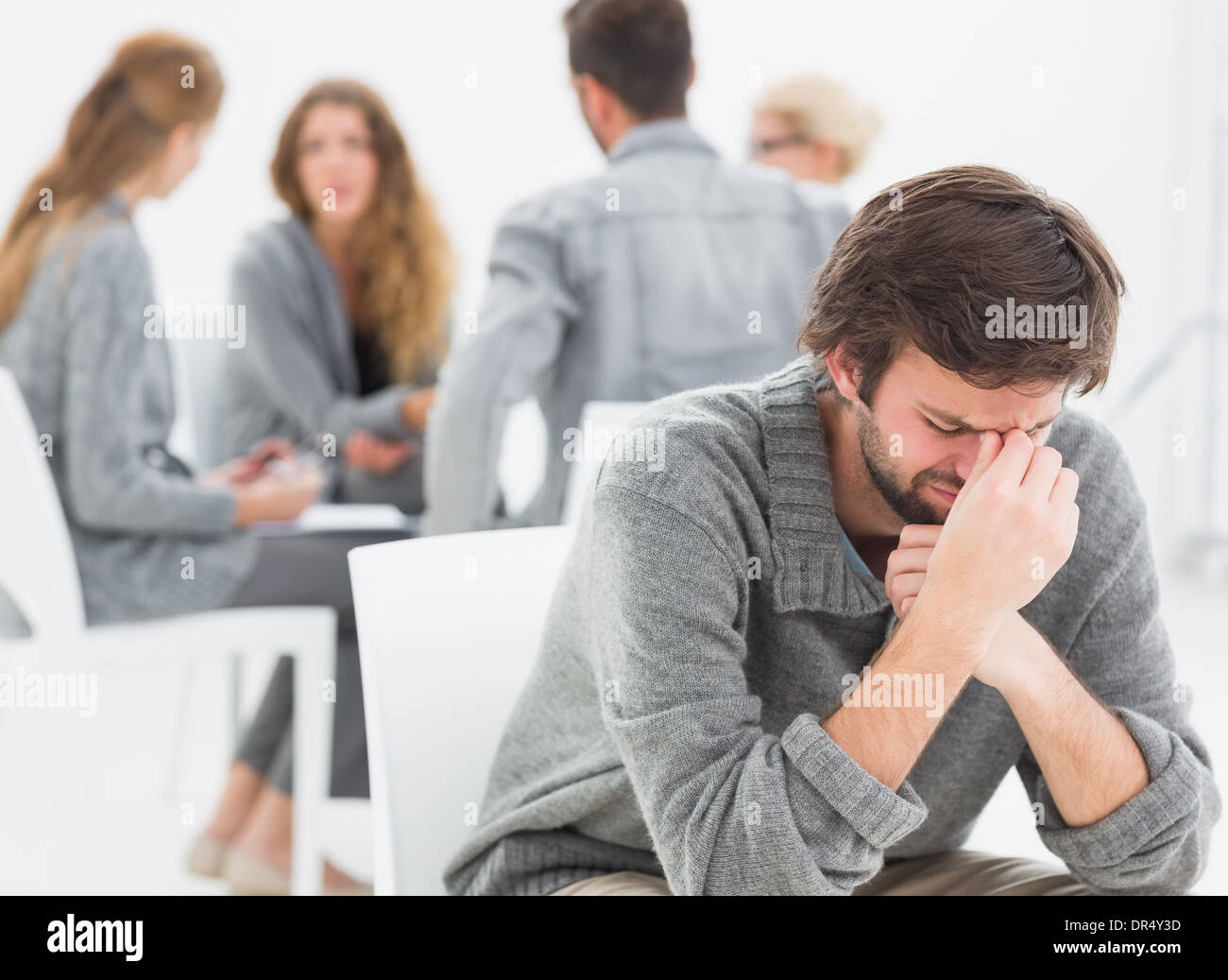 Therapy in session sitting in a circle while man in foreground - Stock Image