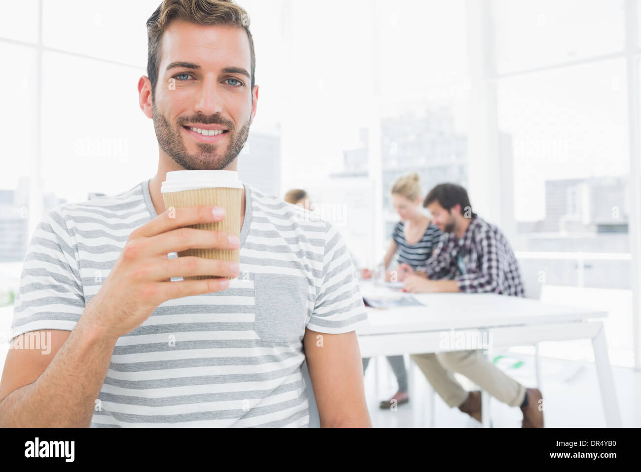 Man holding disposable coffee cup with colleagues in background - Stock Image
