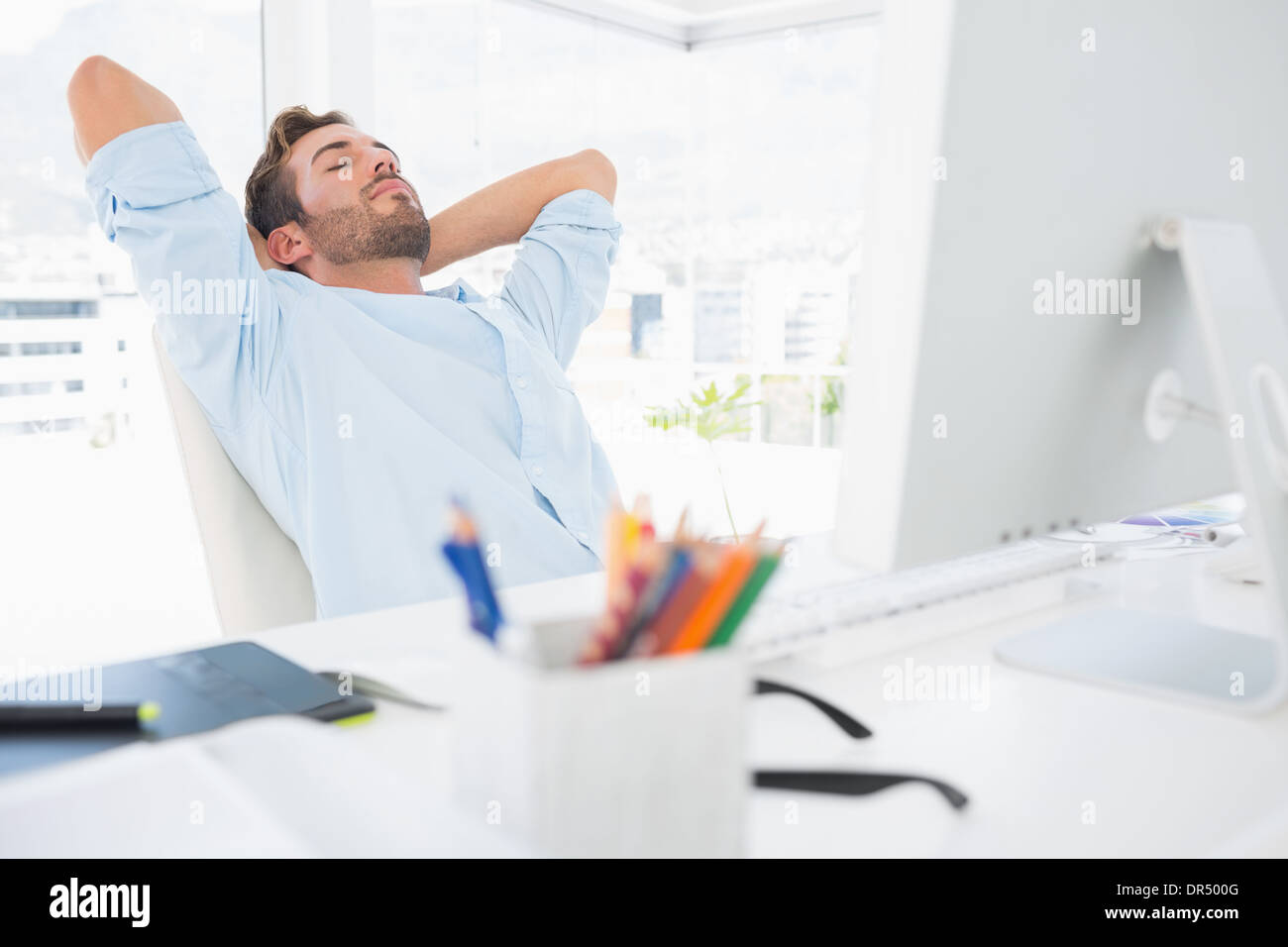 Casual man resting with hands behind head in office - Stock Image