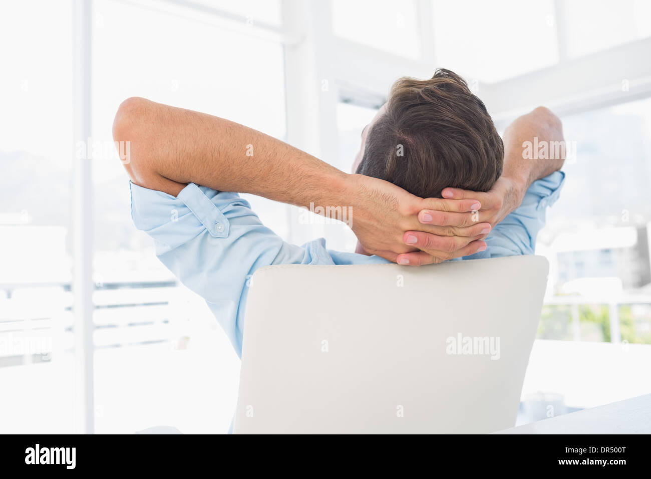 Rear view of a casual man resting with hands behind head in office - Stock Image