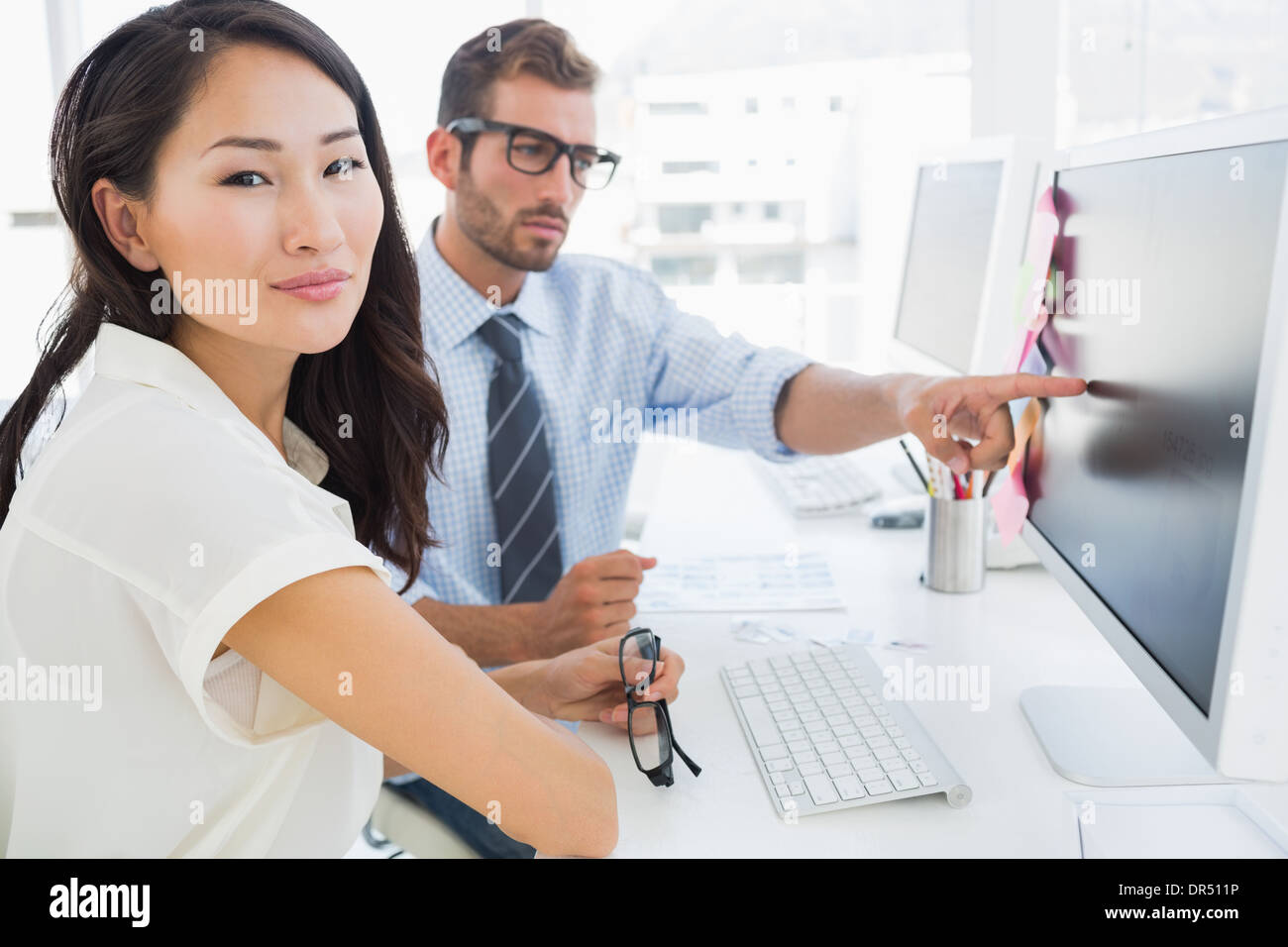 Side view of casual photo editors working on computer - Stock Image