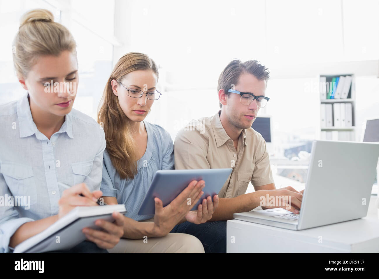 Concentrated three young people in office - Stock Image