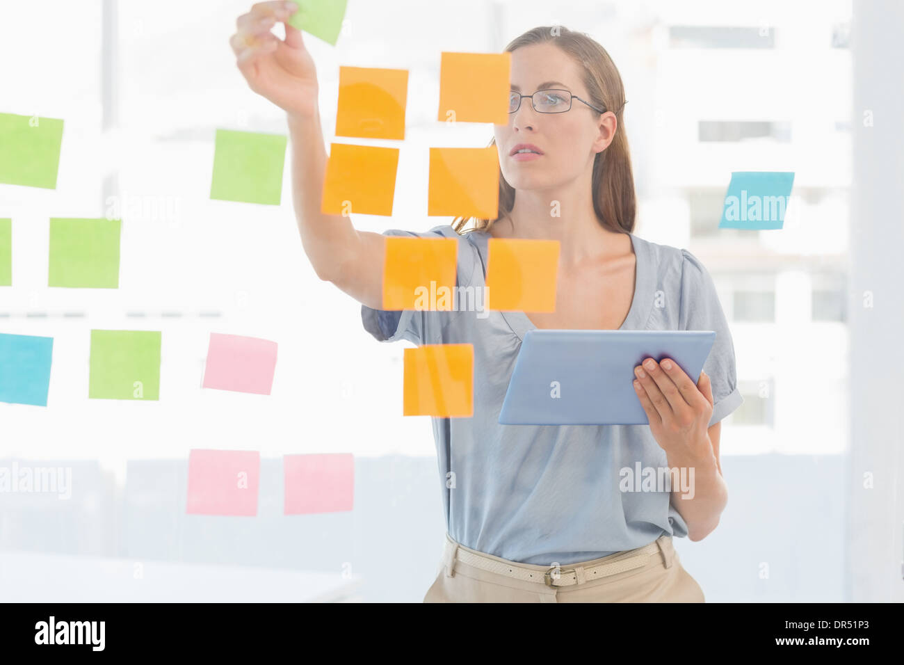 Concentrated artist looking at colorful sticky notes - Stock Image