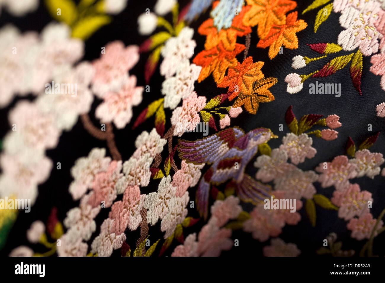 Details of birds and flowers are stitched into silk. Kimonos are the traditional Japanese dress code. However, they are usually worn by older women. Younger adults prefer the modern fashion style. - Stock Image