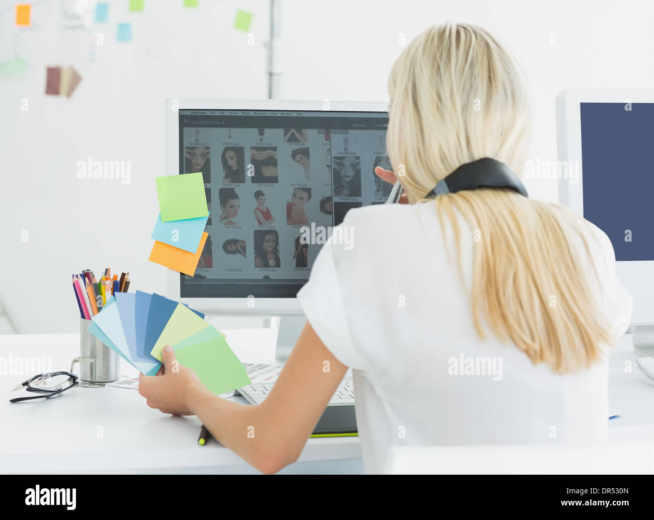 Rear view of a casual woman using computer in office - Stock Image