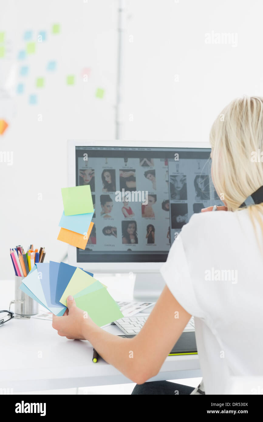 Rear view of casual woman using computer in office - Stock Image
