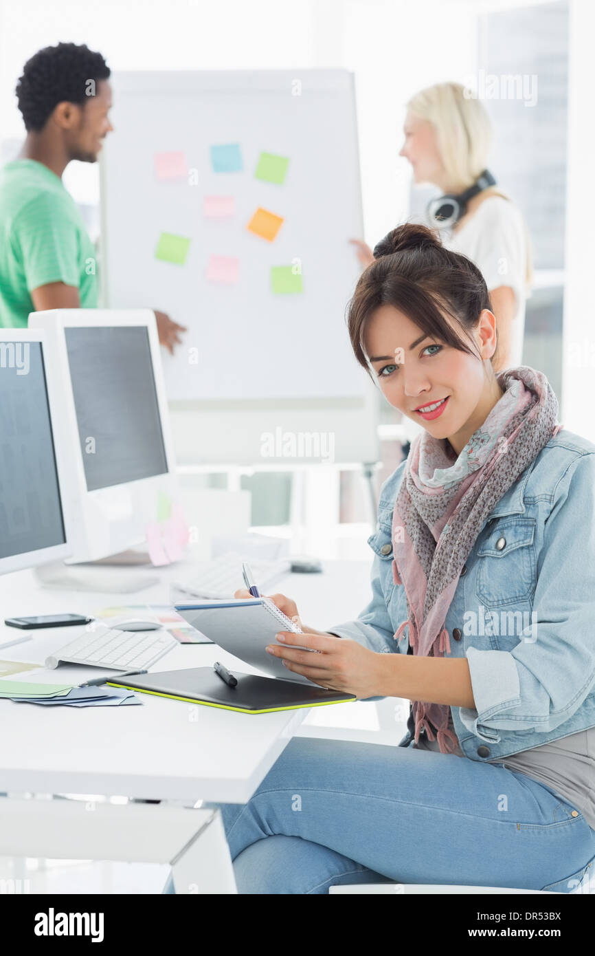 Artist drawing something on graphic tablet with colleagues behind Stock Photo