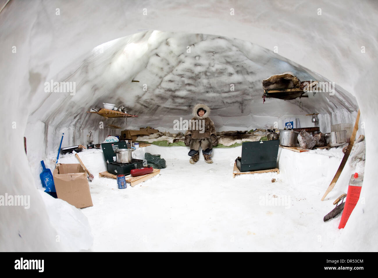A young inuit sits on a bed in an igloo, surrounded by other necessary items to survive in the harsh cold climate. Stock Photo