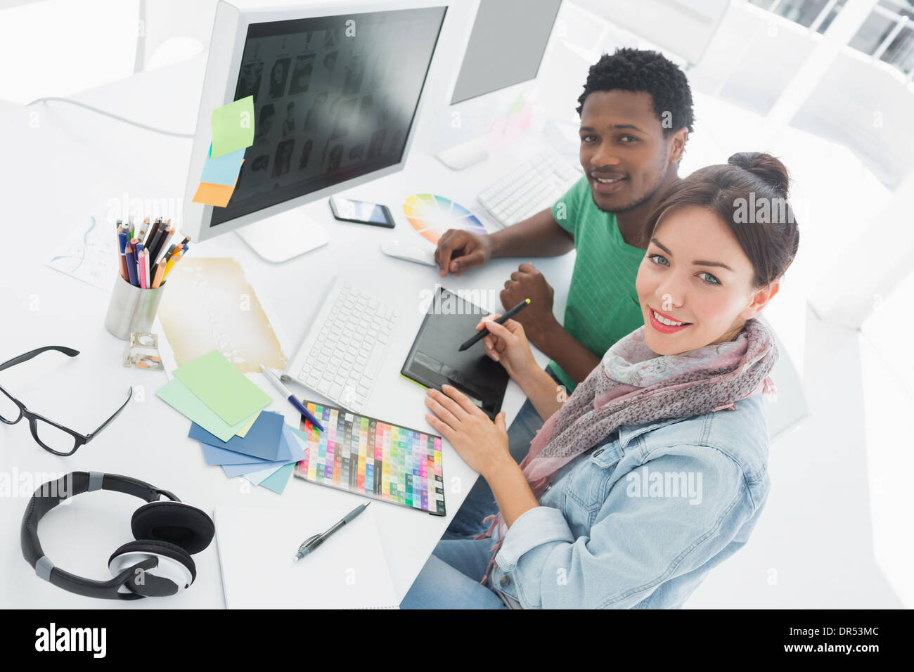 Artist with colleague drawing something on graphic tablet - Stock Image