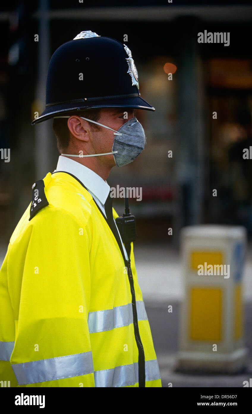A Met Police officer wears a pollution mask while in traffic in central London. - Stock Image