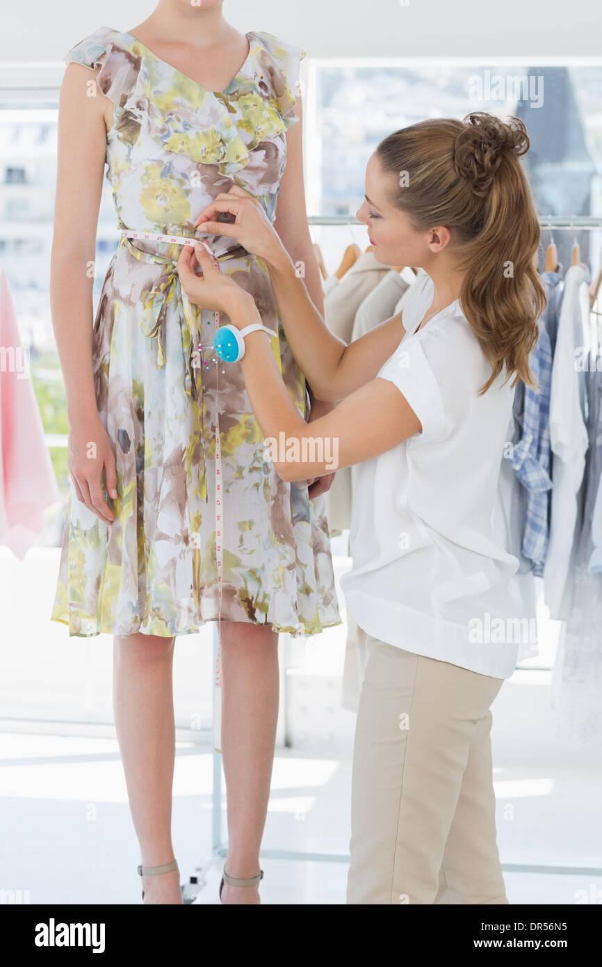 Female fashion designer measuring model's waist - Stock Image