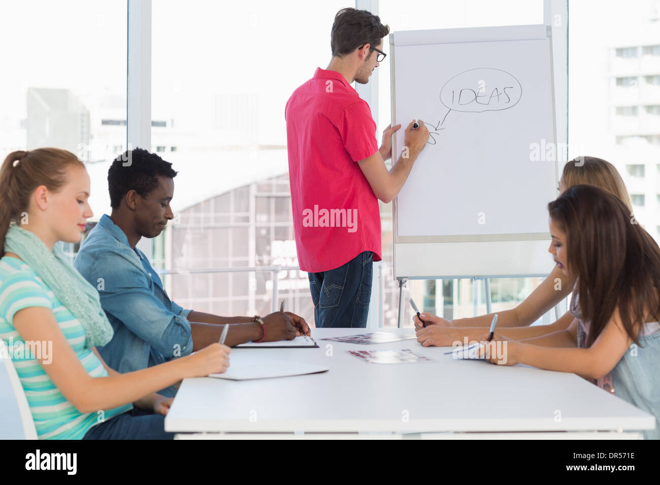 Casual business people in office at presentation - Stock Image