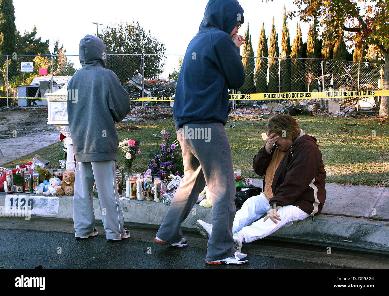 Dec 27, 2008 - Covina, California, USA - DOLORES VILLA, Right, breaks down along with her daughter DONNA JOHNSON and 11 year-old grandson DWIGHT JOHNSON who's aunt and uncle were killed visits the property on Saturday December 27, 2008, in Covina. Bruce Jeffrey Pardo, dressed in a Santa suit, fatally shot nine people during a Christmas Eve party at the Ortega family home before set - Stock Image