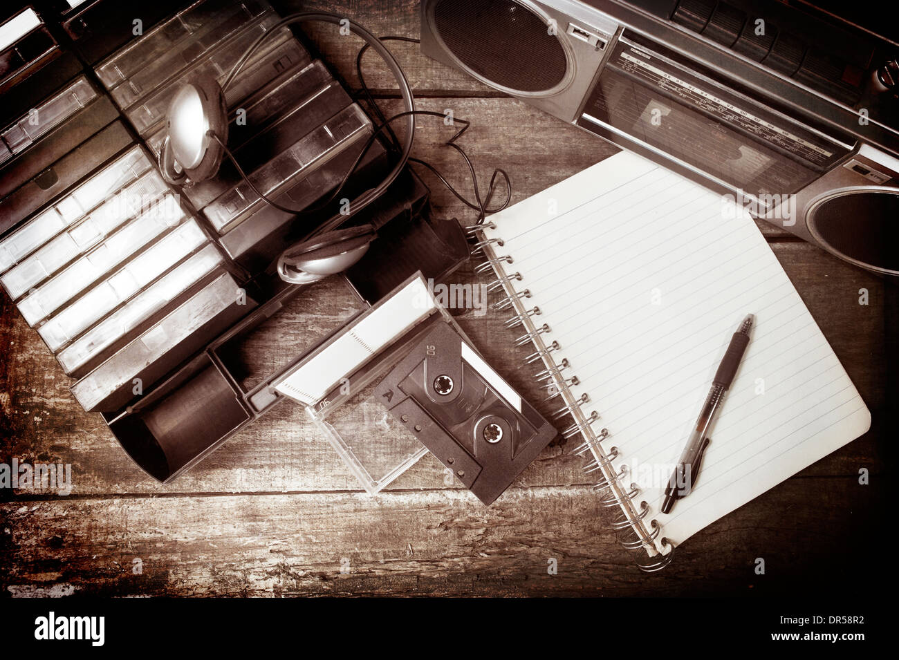 Old cassette tapes, cassette player and blank notebook on wooden surface Stock Photo