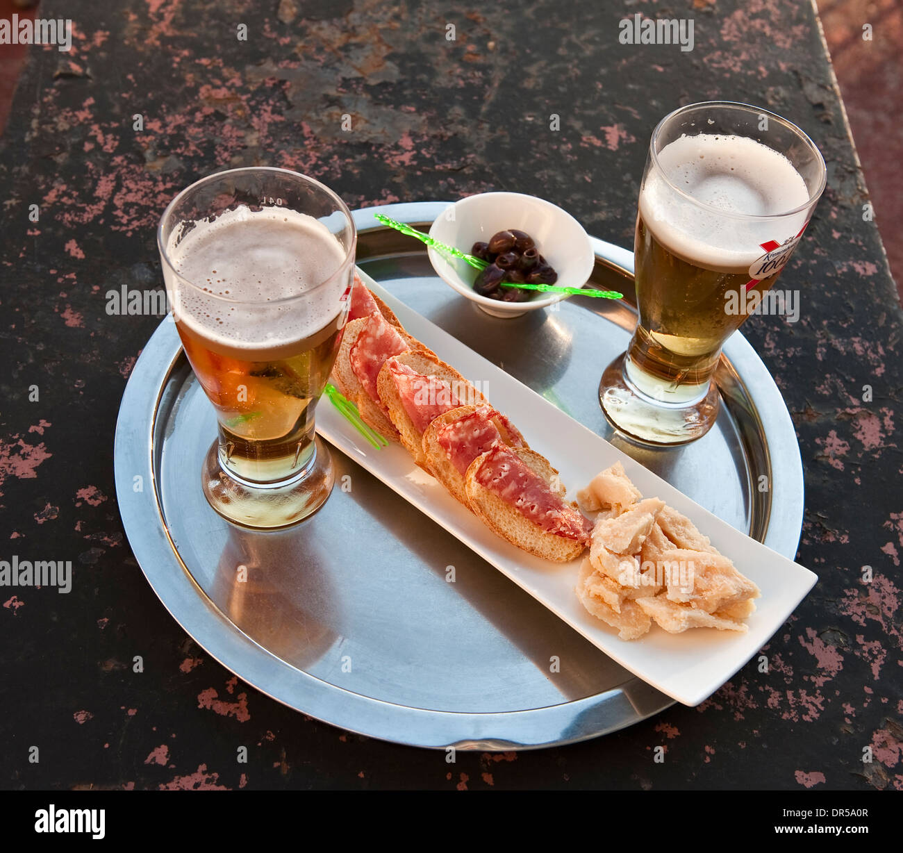 Beer, salami, bread and olives - a light snack at the end of the day on the terrace of a hotel in Italy Stock Photo