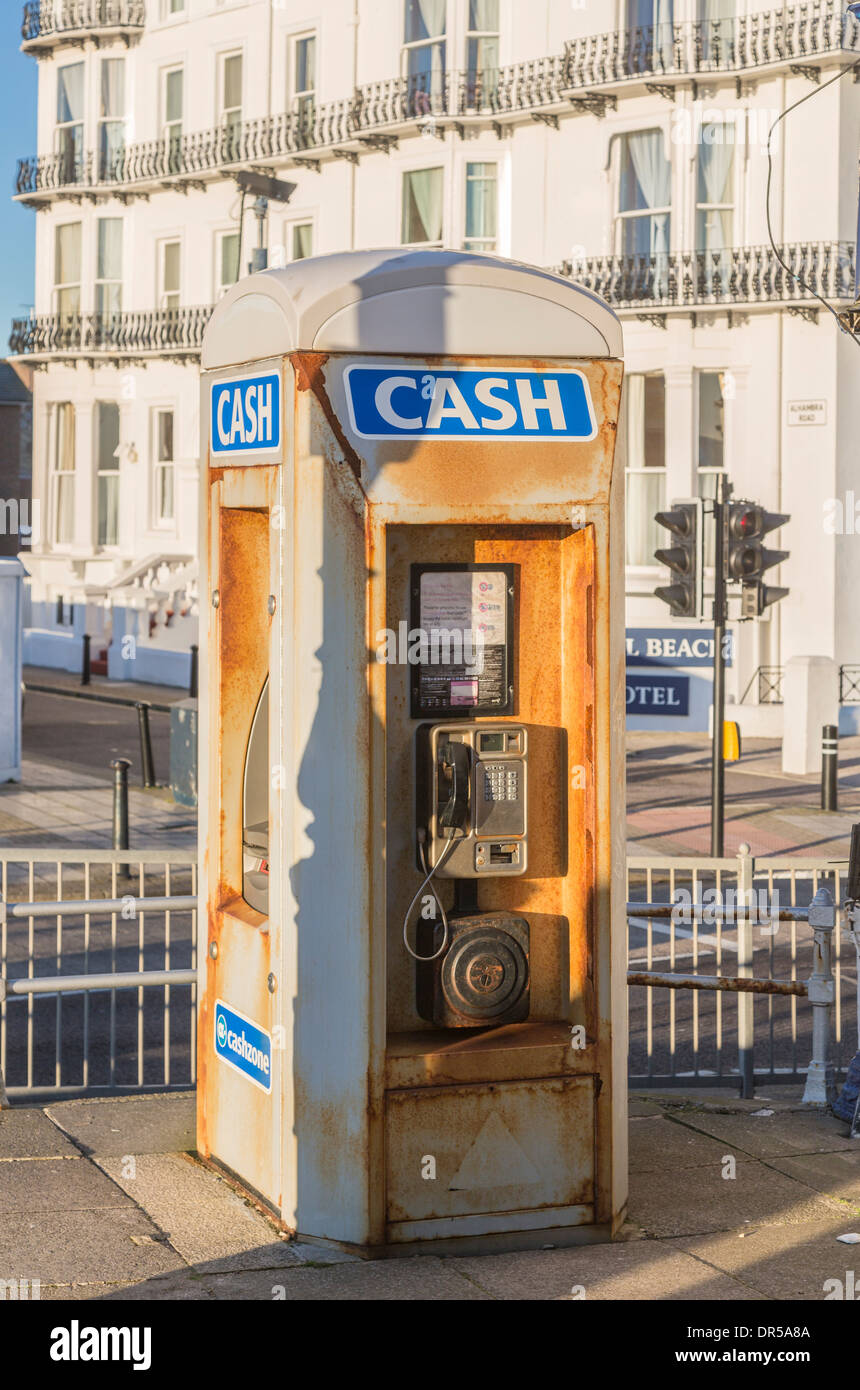 Rusty telephone box with payphone and cash dispenser on seafront in Southsea, Hampshire, England - Stock Image
