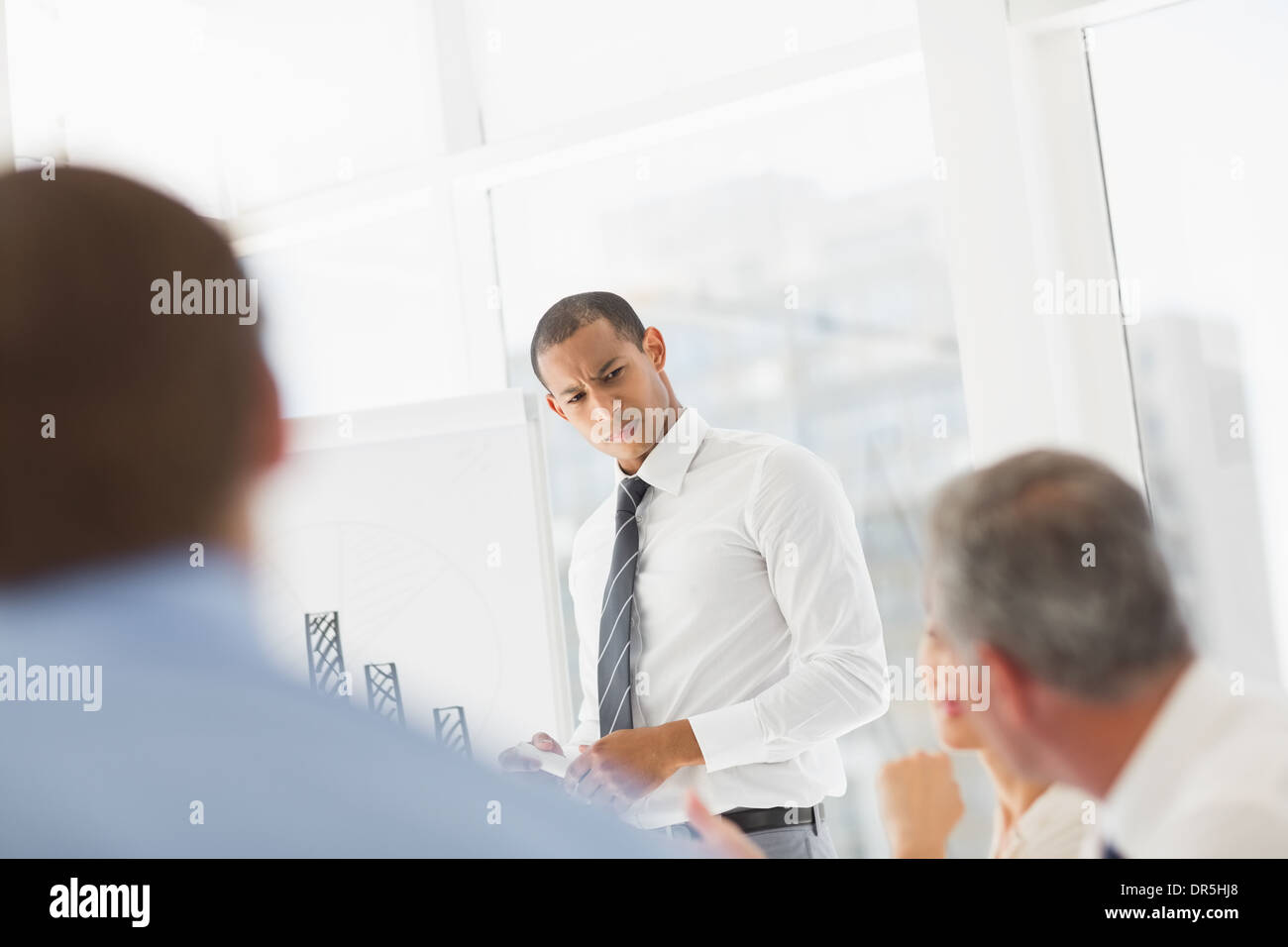 Serious businessman presenting bar chart to co workers - Stock Image