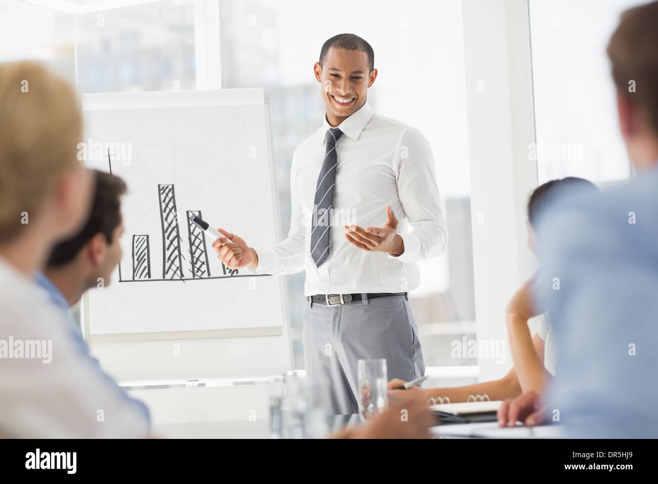 Happy young businessman presenting bar chart to co workers - Stock Image