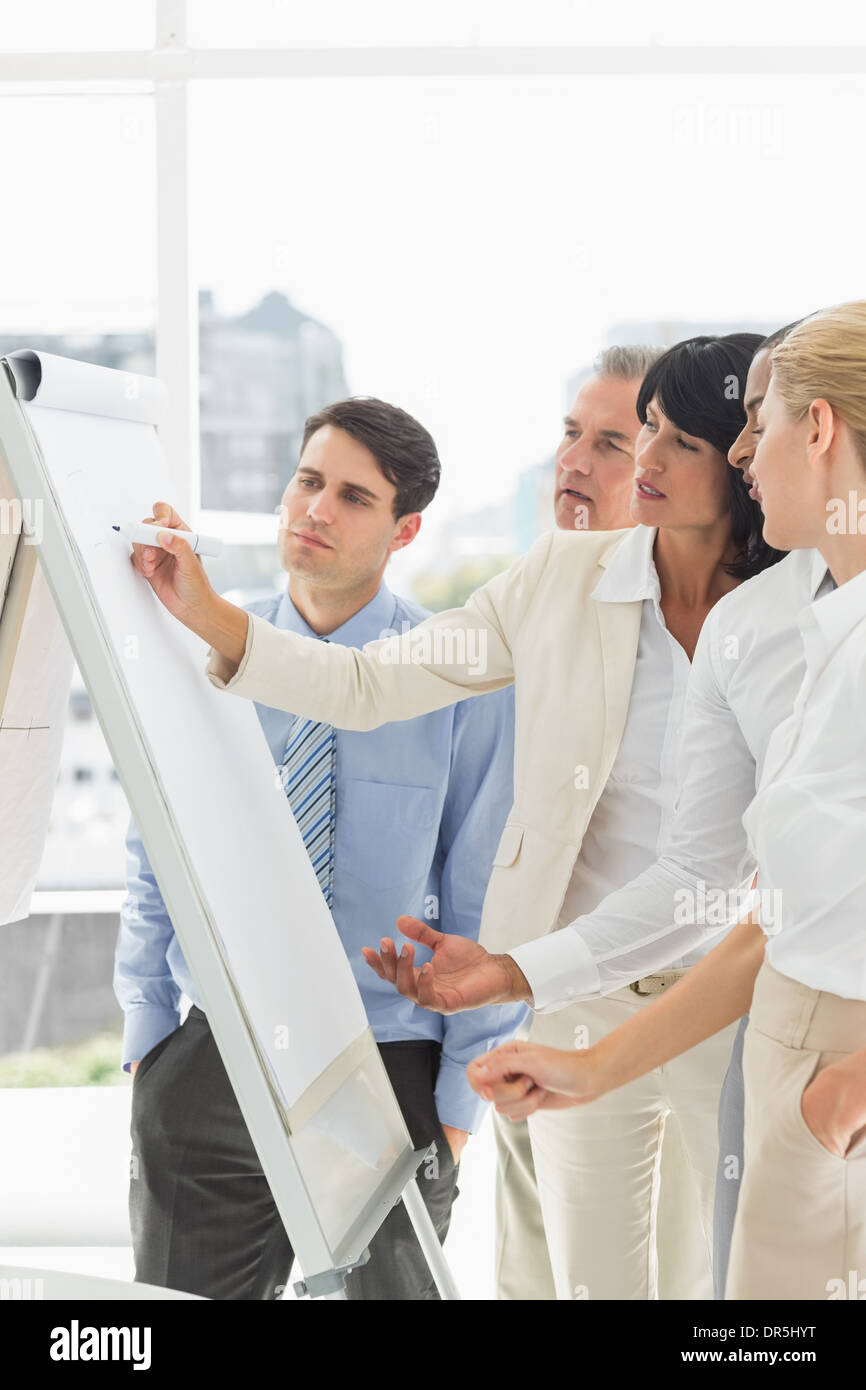 Interested colleagues watching businesswoman writing on whiteboard - Stock Image