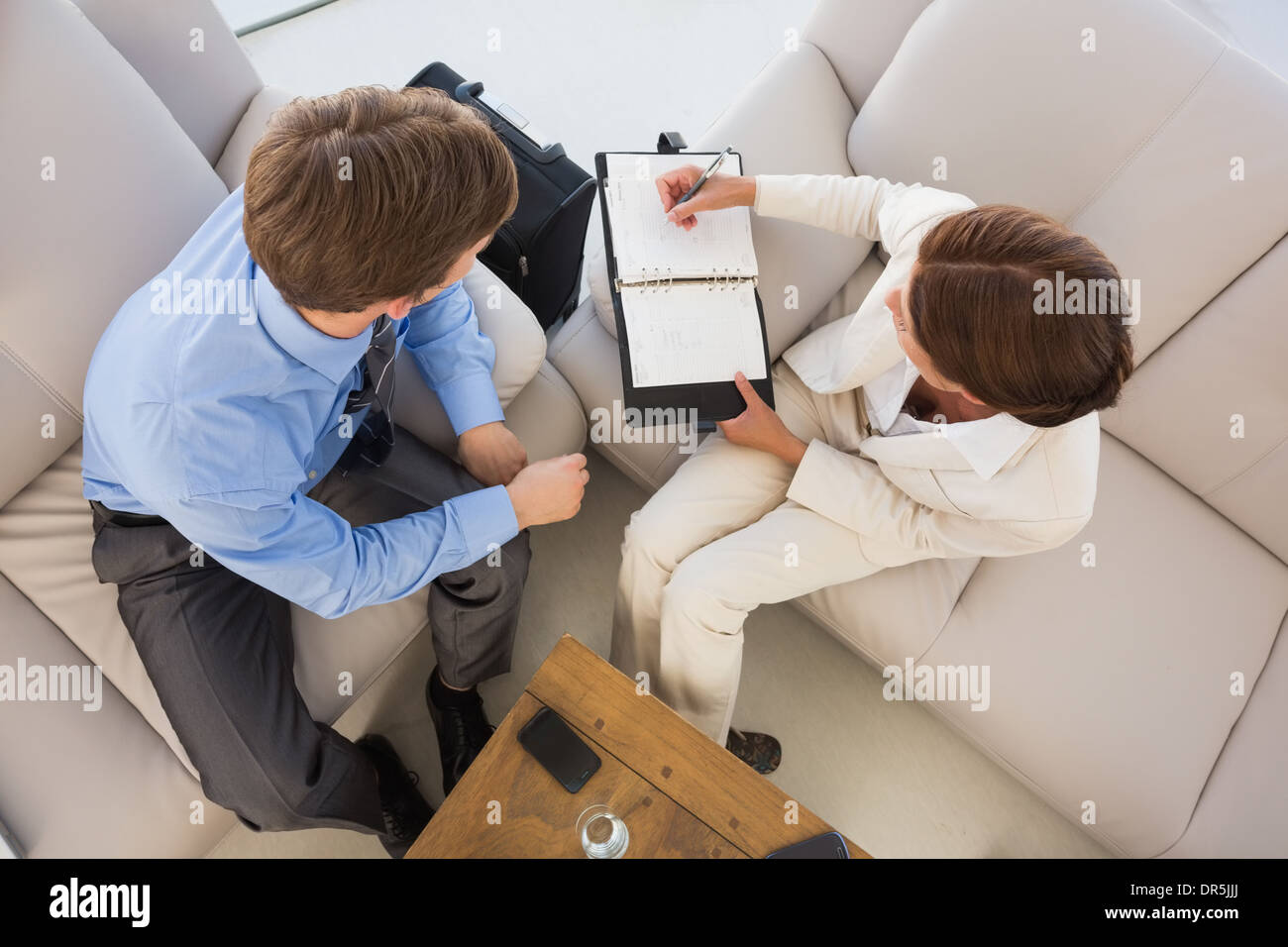 Business team working together on the couch scheduling in diary - Stock Image