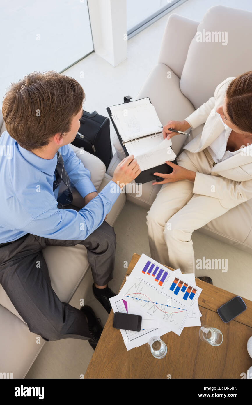 Business team working on the couch scheduling in diary - Stock Image