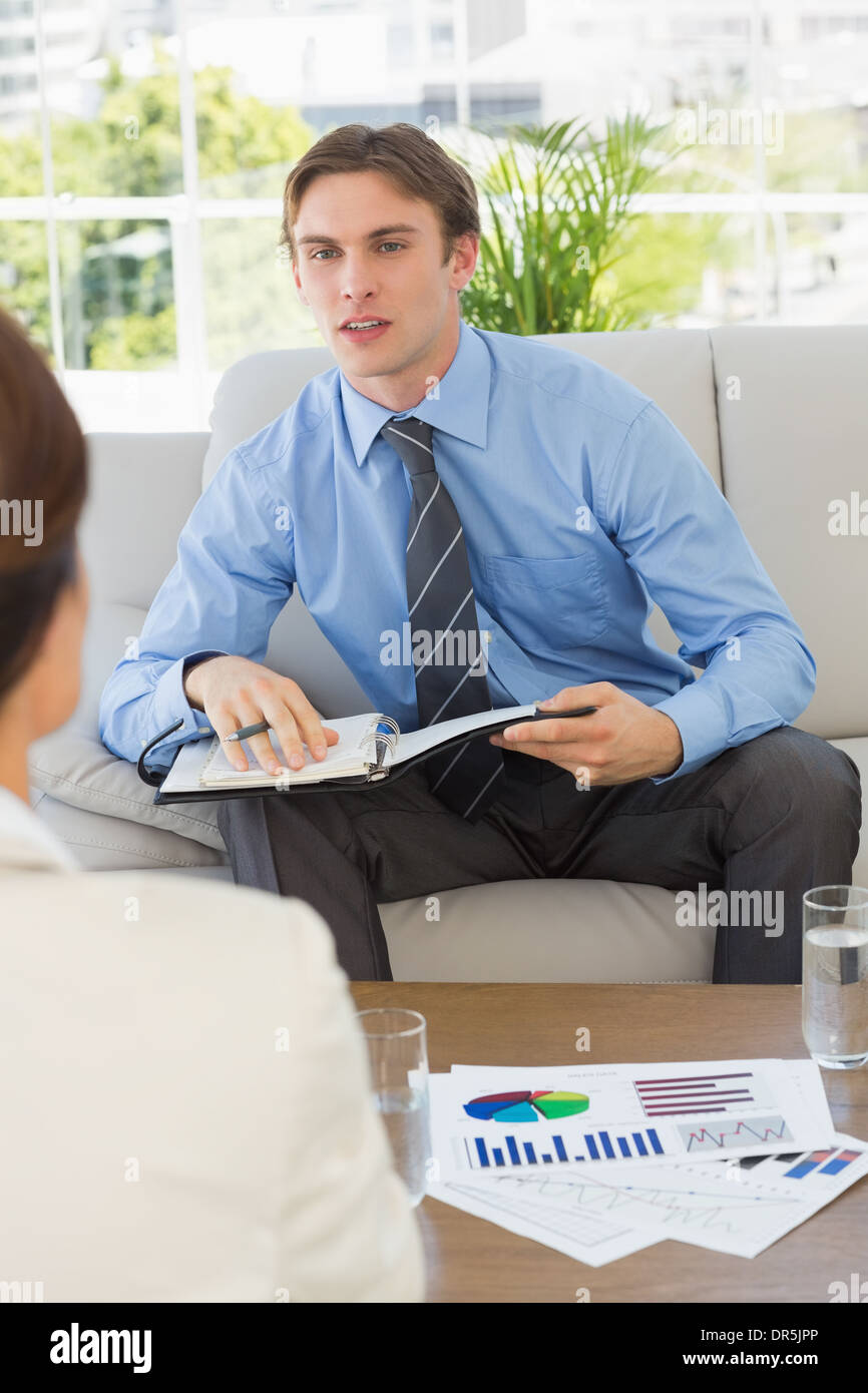 Businessman scheduling with colleague sitting on sofa - Stock Image