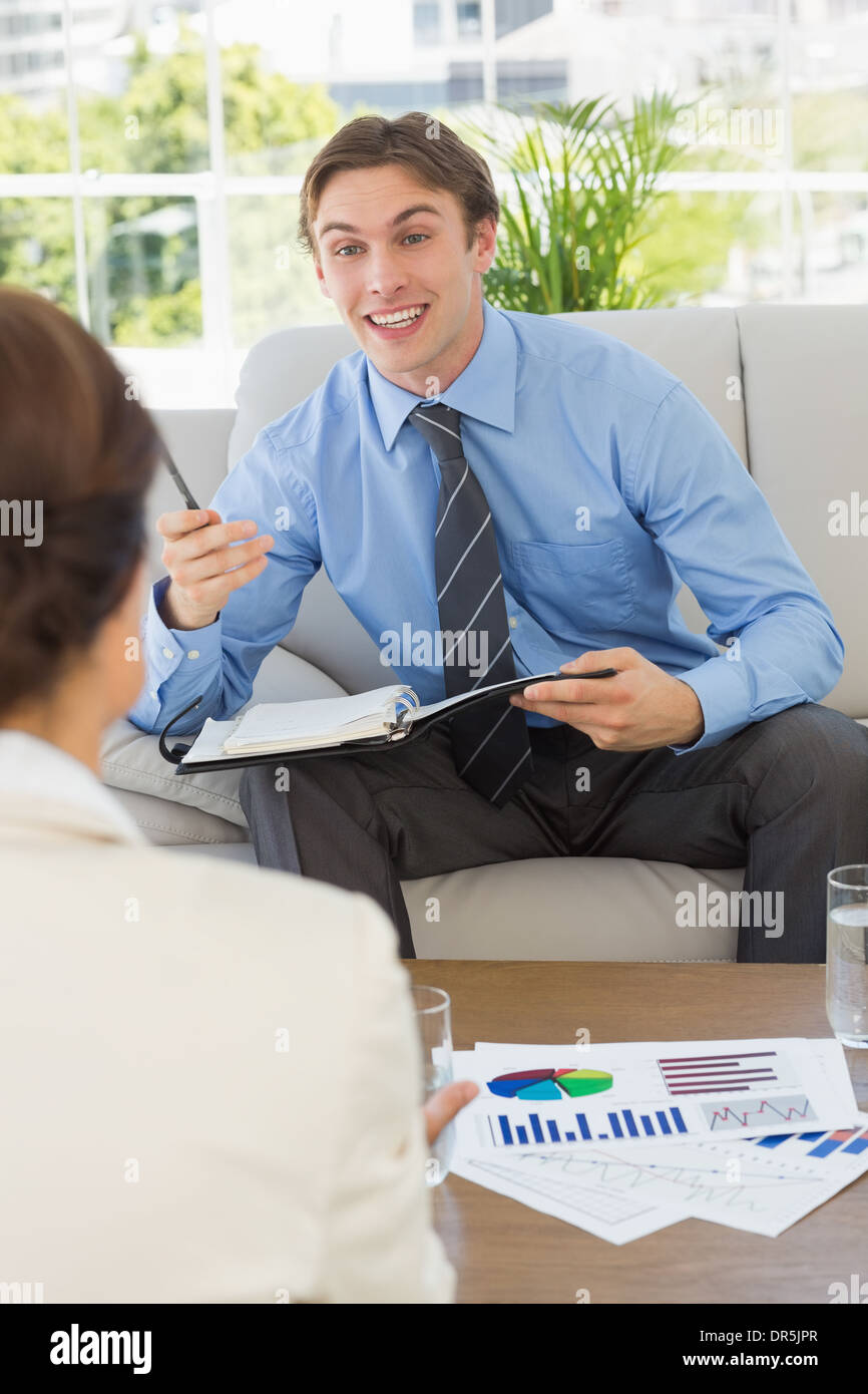 Happy businessman scheduling with colleague sitting on sofa - Stock Image