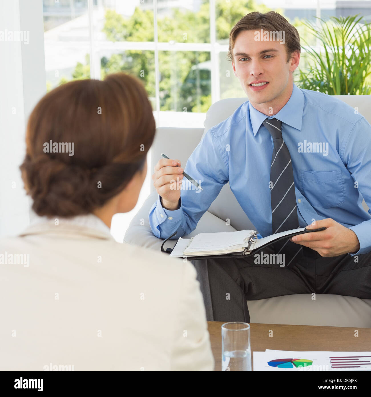 Young businessman scheduling with colleague sitting on couch - Stock Image