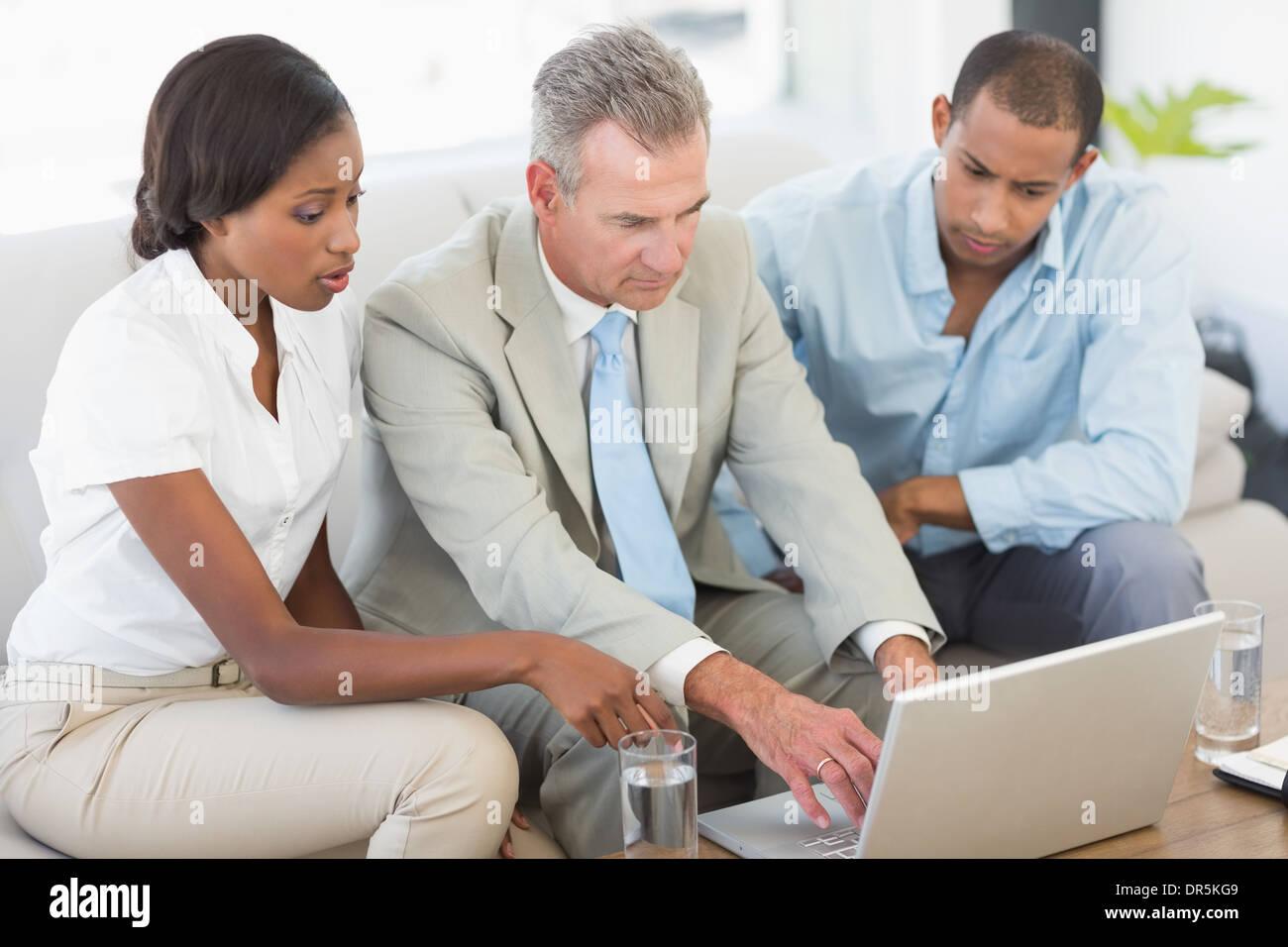 Salesman showing something on laptop to couple on sofa - Stock Image