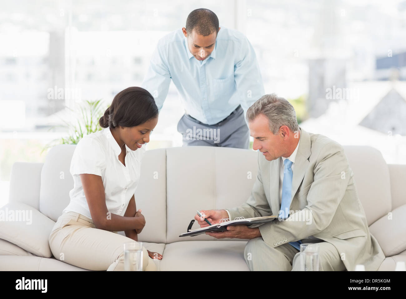 Salesman showing client where to sign the paperwork - Stock Image